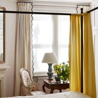 Yellow Curtained Bed with Embroidered Bedspread