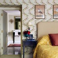 Braquenié wallpaper with yellow bedspread and antique prints