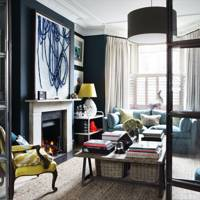 Living room with navy blue walls and white curtains