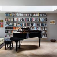 Modern living room with piano and bookshelves