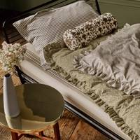 Olive green bedroom with frilled eiderdown