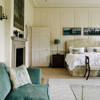White panelled Bedroom with Green Sofa