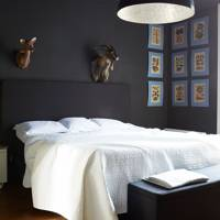 Dark blue bedroom with white bed