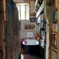 Bathroom with bookshelves in a magical barn conversion