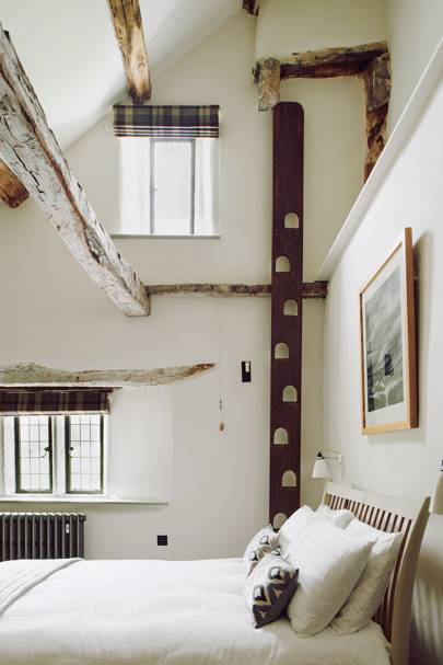 Small white bedroom with wooden beams