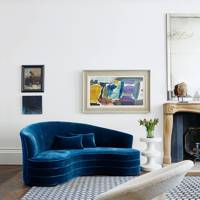 Modern white living room with curved blue sofa