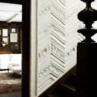 Dark wood stairs with decorative plasterwork walls