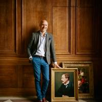 James Bilderbeck, managing director of Family Copies, with two recreated paintings: a portrait of a client's ancestor and Still Life with Flowers and Fruit (1827) by Jan Frans van Dael.