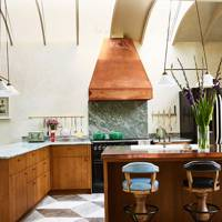 Kitchen with copper cooker hood and worktop