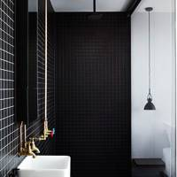 Bathroom with exposed brass pipes and black tiles