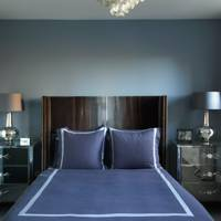 Small blue bedroom with mirrored bedside tables